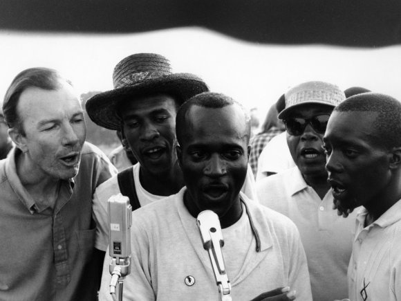 """Pete Seeger, teaching """"We Shall Overcome"""" at civil rights protests and rallies. Greenwood, Mississippi. 1963. Photo by Adger Cowans / Getty Images."""